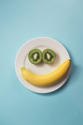 Smiling face made from banana and kiwis