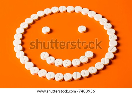 Smiling face made up out of white tablets on the orange background