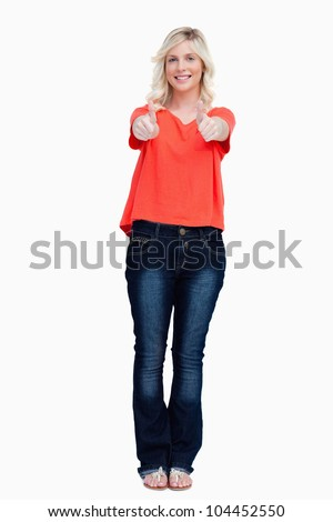 Smiling fair-haired teenager showing her thumbs up against a white background