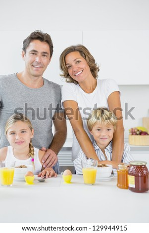 Smiling family at breakfast in the kitchen stock photo