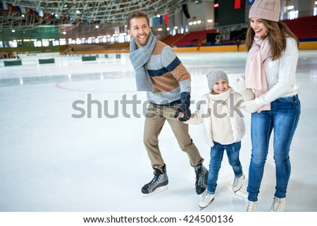 Smiling family at ice-skating rink - Shutterstock ID 424500136