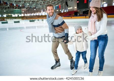 Smiling family at ice-skating rink