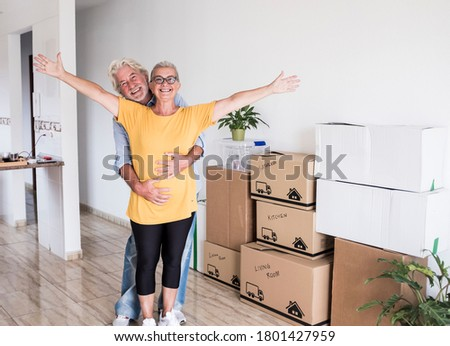 Smiling family couple of two senior people happy of new home for new beginning like retired with moving boxes on the floor