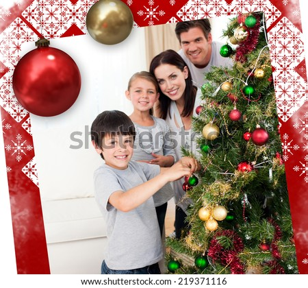 Smiling family decorating a Christmas tree against christmas themed page