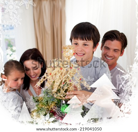 Smiling family decorating a Christmas tree at home against christmas frame