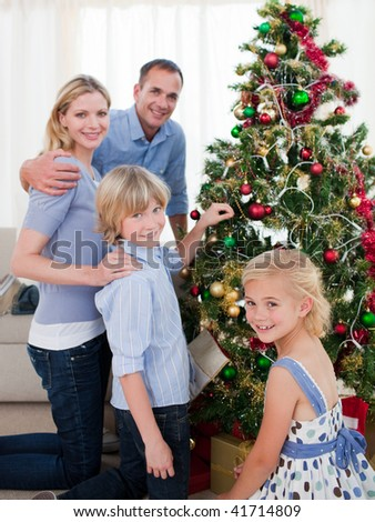Smiling Family hanging decorations on a Christmas tree at home