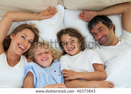 Smiling family having fun lying in the bed