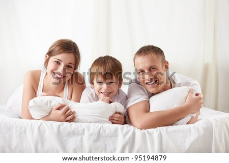 Smiling family in a bedroom at home