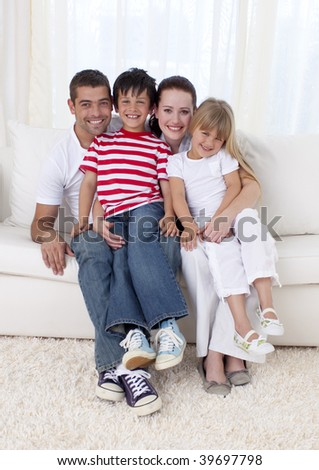 Smiling family in living-room sitting on sofa together