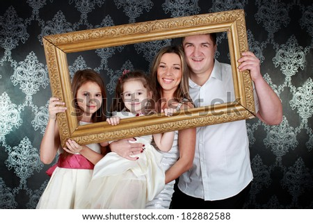 Smiling family looking through an empty frame