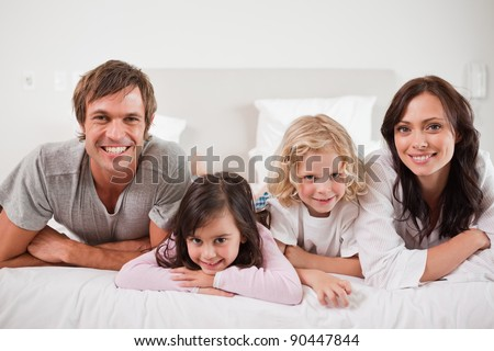 Smiling family lying in a bed together