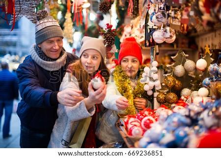 Smiling family of three choosing Christmas decoration at  Christmas market