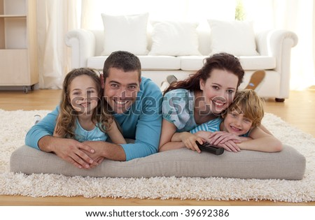 Smiling family on floor lying in living-room