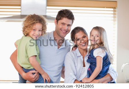 Smiling family posing in their kitchen