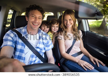Smiling family sitting in the car and driving