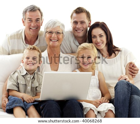 Smiling family sitting on sofa using a laptop at home