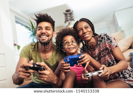 Smiling family sitting on the couch together playing video games #1140153338