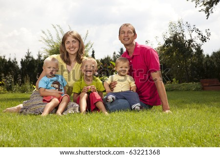 Smiling family sitting outdoors