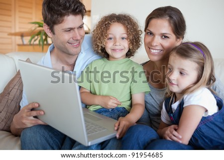 Smiling family using a laptop in their living room