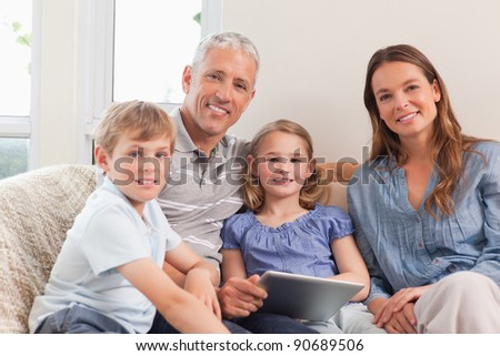 Smiling family using a tablet computer in a living room