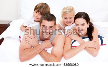 Smiling family waching television at home