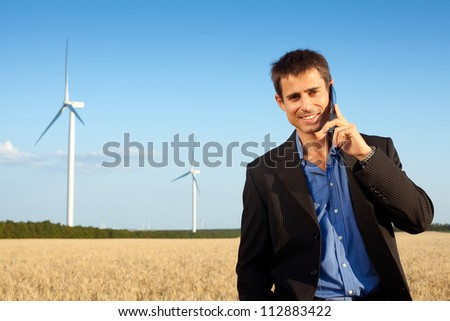 smiling farmer (businessman) standing in wheat field over wind turbines background and speaking on mobile phone