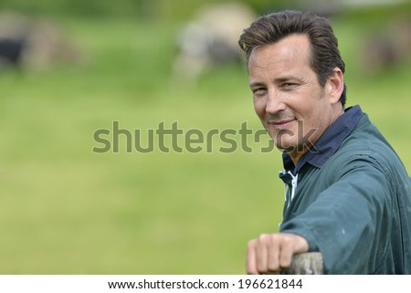 Smiling farmer standing in country field