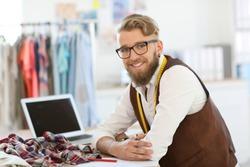 Smiling fashion designer working in studio