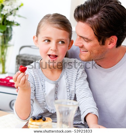 Smiling father and his daughter having breakfast together in the kitchen