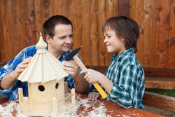 Smiling father and son building a wooden bird house together