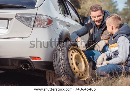 smiling father and son changing car wheel together Imagine de stoc ©