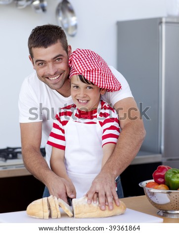 Smiling father and son cutting bread in kitchen