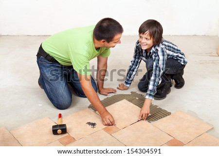 Smiling father and son laying ceramic floor tiles together