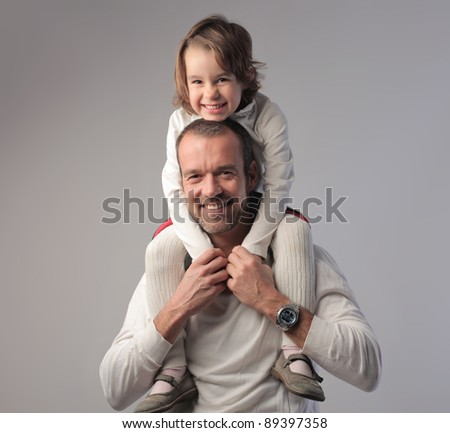 Smiling father carrying his daughter on his shoulders