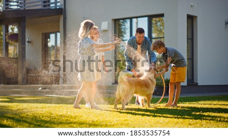 Smiling Father, Daughter, Son Play With Loyal Golden Retriever Dog, Spraying Each other with Garden Water Hose. On a Sunny Day Family Having Fun Time Together Outdoors in Backyard.