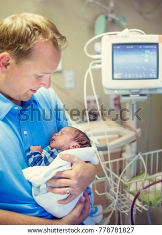 Smiling father holding his newborn baby son in a hospital room Foto stock ©