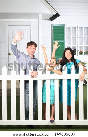 Smiling father, mother and little daughter wave their hands next to white wooden fence near house.