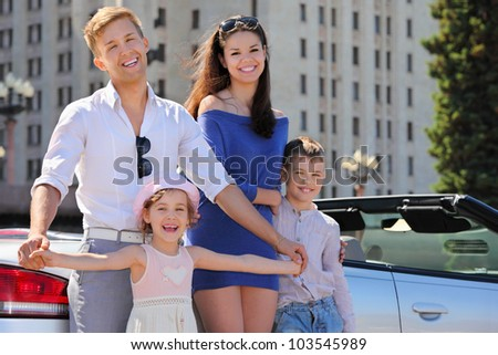 Smiling father, mother and two children stand near convertible car - stock photo
