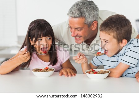 Smiling father talking with his children during their breakfast in kitchen