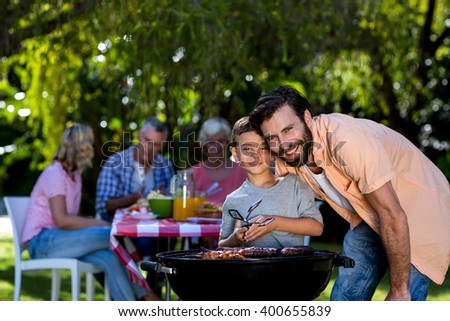 Smiling father with son by barbecue grill against family in yard