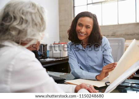 Smiling female analyst in consultation with senior woman #1150248680