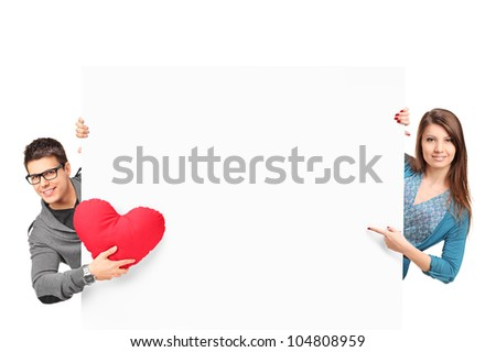 Smiling female and male with heart shaped object posing behind a white panel isolated on white background