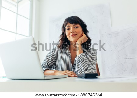 Smiling female architect working on laptop in office. Entrepreneur sitting at workplace with architecture drawings in the background.