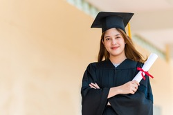 Smiling female Asian student in academic gown and graduation cap holding diploma