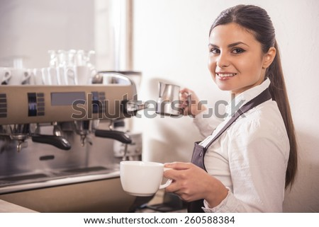 Smiling female barista is preparing coffee at coffee shop.