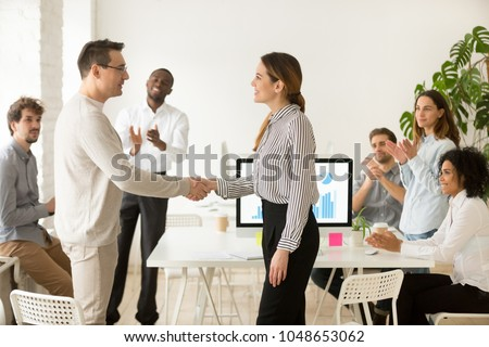 Smiling female boss promoting rewarding handshaking motivated worker showing respect while team applauding congratulating colleague at group meeting, appreciation and employee recognition concept
