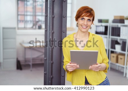 Smiling female business owner with red hair and wearing a yellow shirt checks inventory while leaning against steel beam