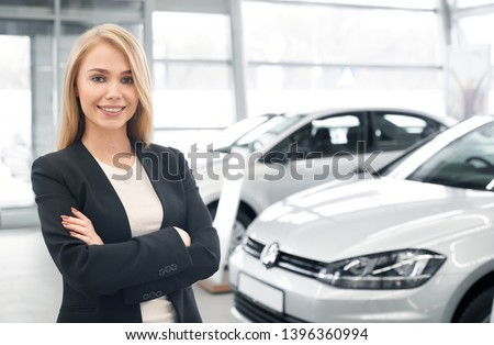 Smiling female car dealer with folded arms looking at camera and posing in front of new automobiles. Pretty woman wearing smart suit working in auto salon and selling cars to clients. #1396360994