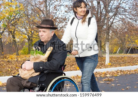 Smiling Female Carer Pushing An Old Handicapped Man In A Wheelchair Along The Street As They Return From Doing His Grocery Shopping