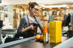 Smiling female cashier scanning grocery items at supermarket